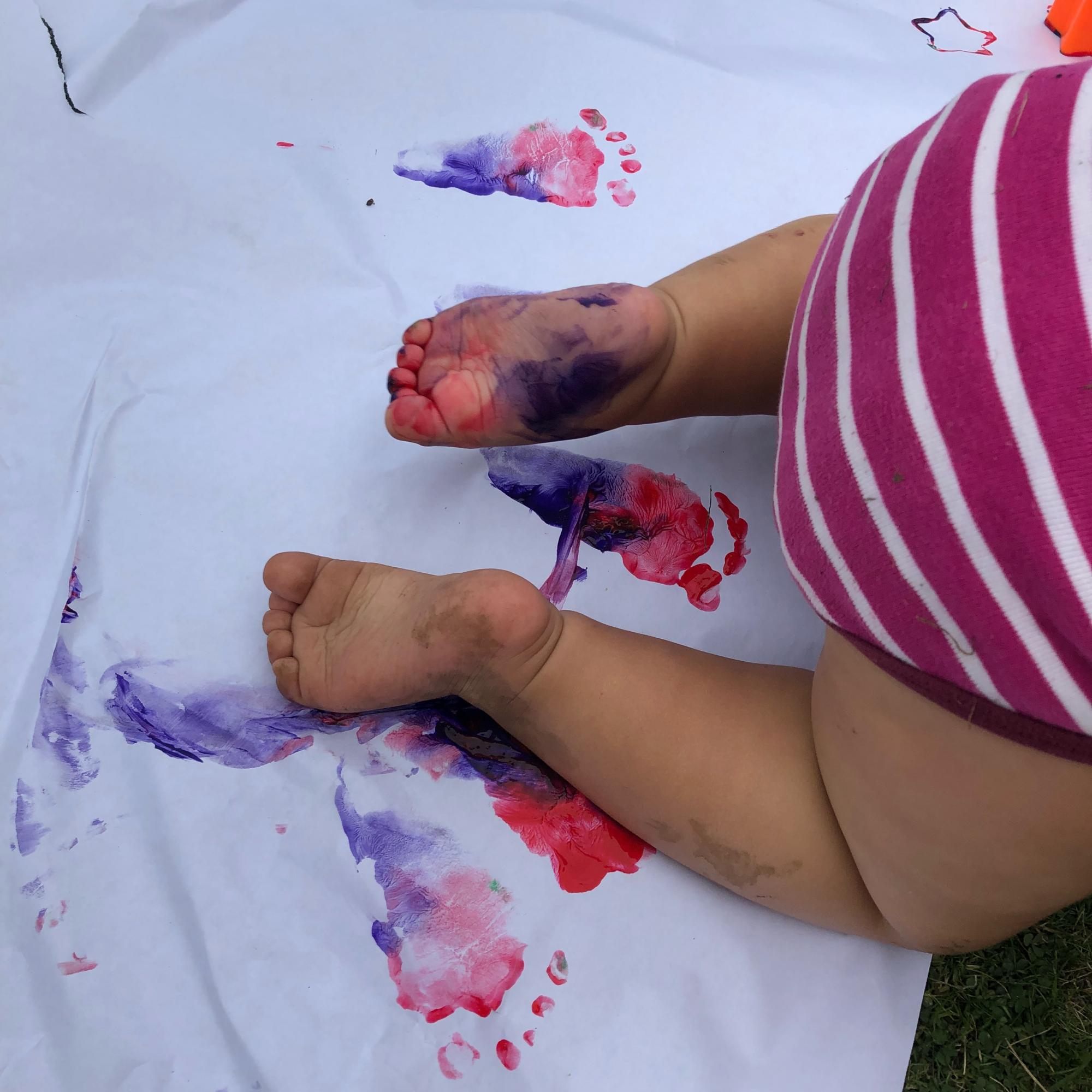 Baby crawling with paint on their feet doing an art activity on grass.